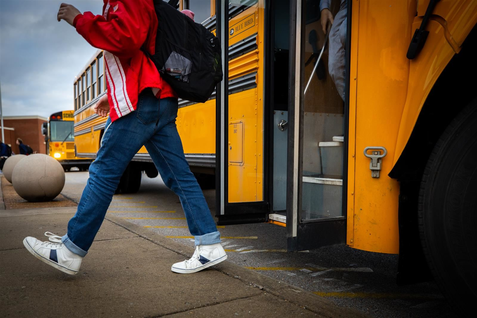 A boy walks off a school bus.