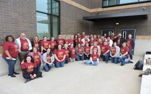 Faculty and staff posing as a group in front of new building.