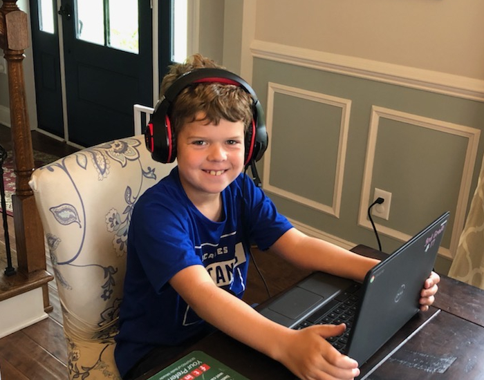 Young student learning from his laptop with headphones on