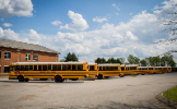 School busses are parked in front of school