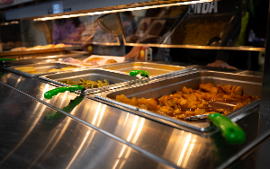 Hot trays of food in cafeteria serving line