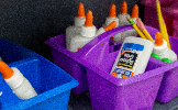 Blue and purple buckets filled with glue bottles and pencils