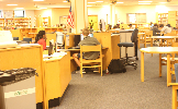Students studying and working at various locations in the media center.