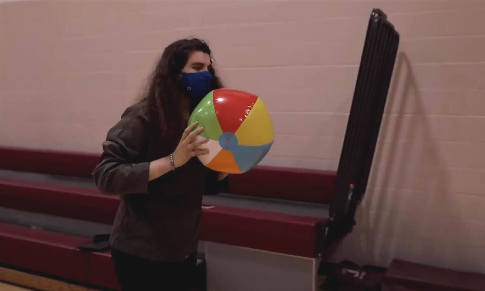 Girl throws beach ball