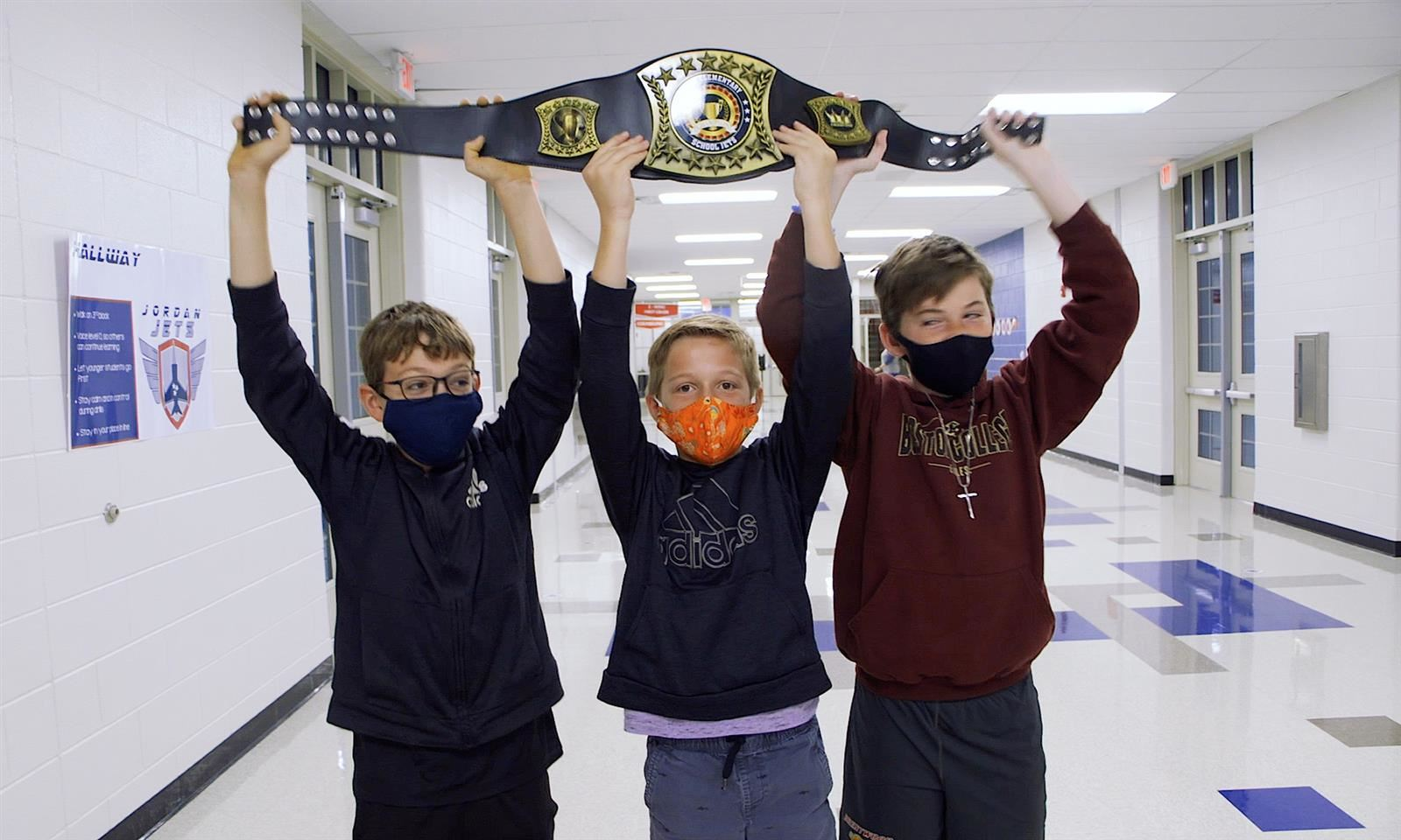 Students hold up belt