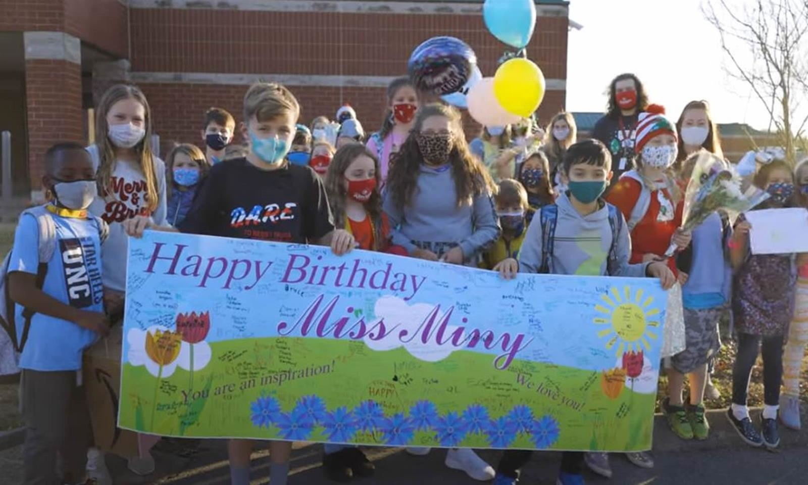 Students hold birthday signs