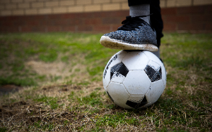 Foot on top of a soccer ball