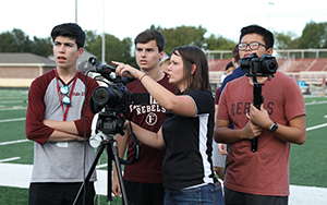 TV and Film teacher with students filming football game