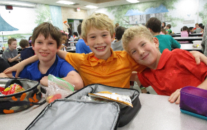Three boys eating lunch in the lunch room