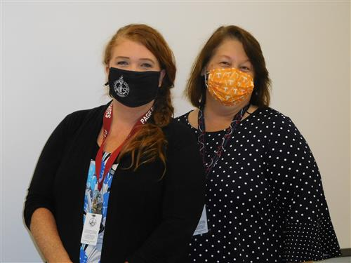 Two teachers standing side by side with masks on.