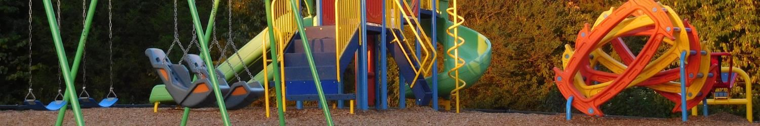 elementary school playground with swings, a jungle gym, and climbing structure
