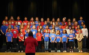 fourth and fifth grade students singing in a choir on a school stage