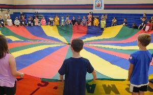elementary school students playing with a parachute in a school gym