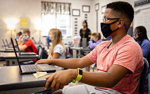 Student wearing mask sitting at desk with computer sitting on it