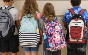 Four kids wearing backpacks standing and facing a wall.