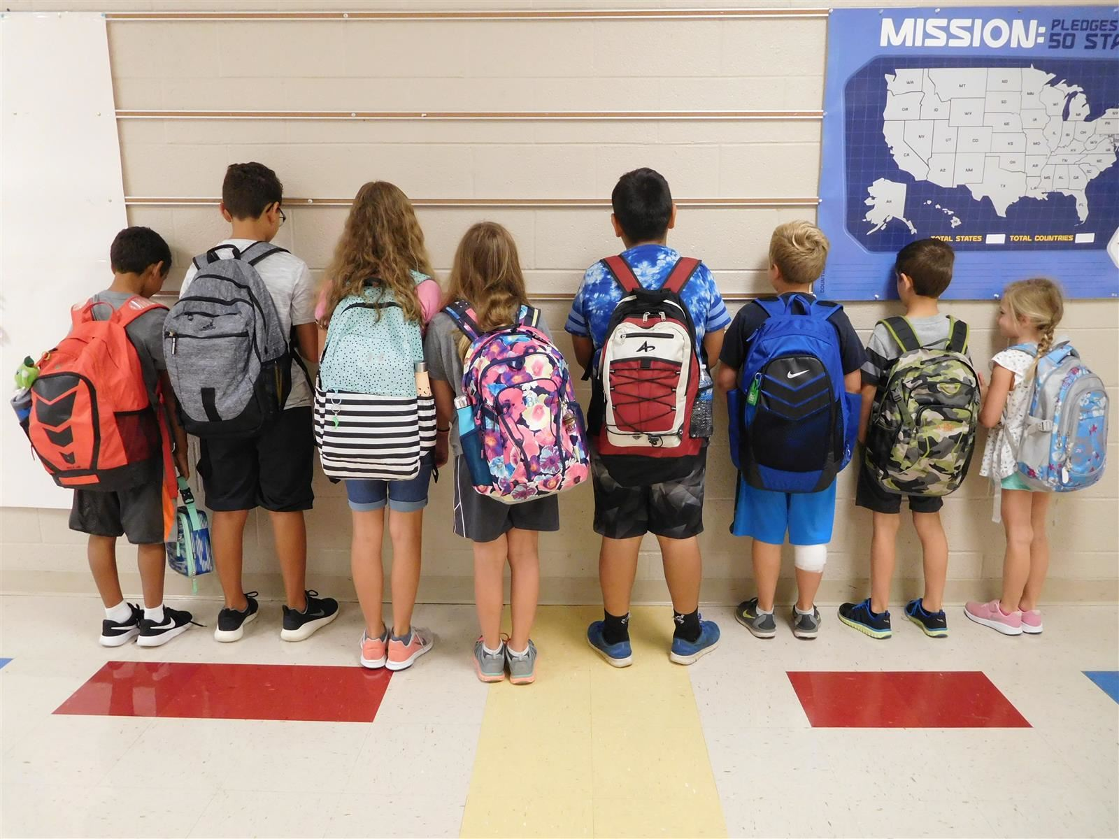 Kids standing facing wall with backpacks showing