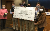 Students holding the $800 prize check