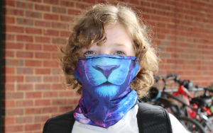 Boy wearing a tiger face mask outside of school