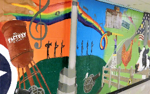 A mural in Page High School with various images, such as farm animals and the Tennessee state fl