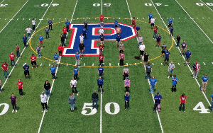 Picture of the Page High faculty standing in lines on the Page High football field.