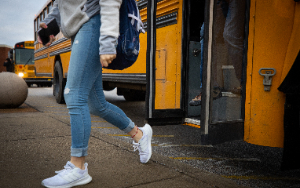 Girl student walking off bus