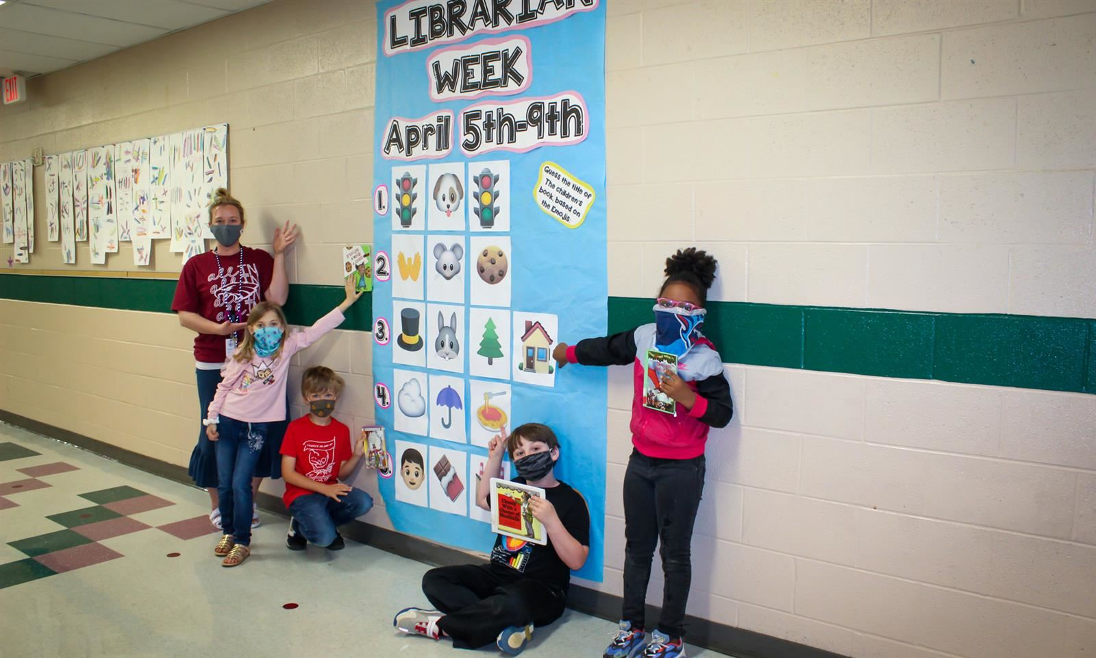 Students stand against wall with Library Week sign