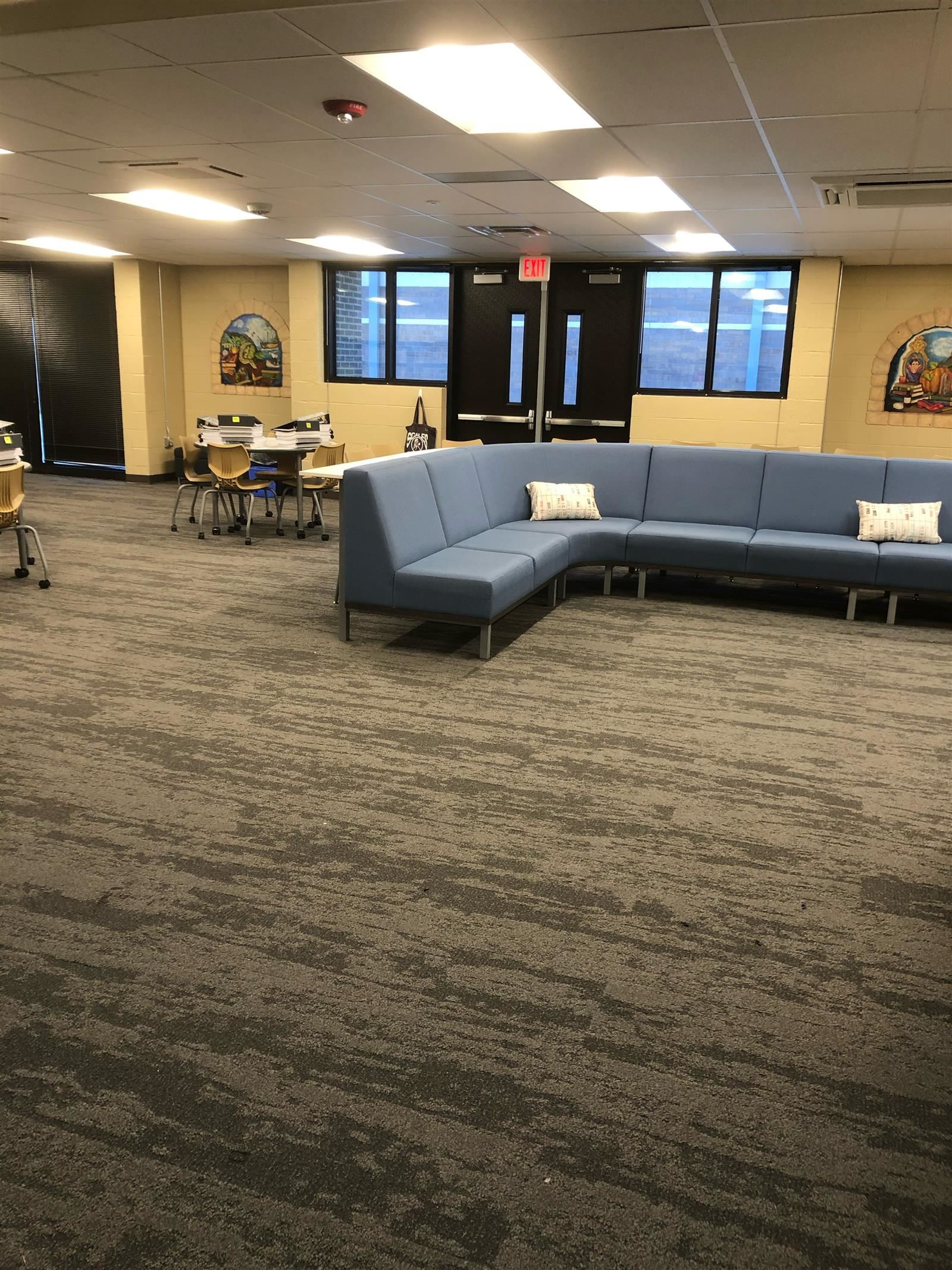 Half moon couch with tables and chairs in the SES Learning commons