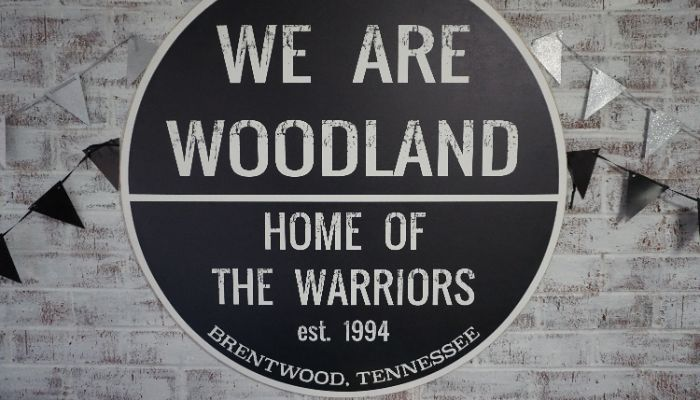 Image shows some of Woodland faculty in front of Reward School Banner.
