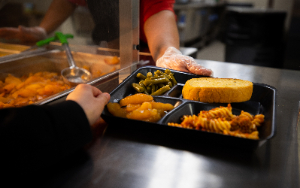 Image shows student receiving lunch tray in cafeteria.